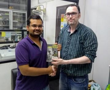 Shyam Verma presenting a book to Ujjwal Jain